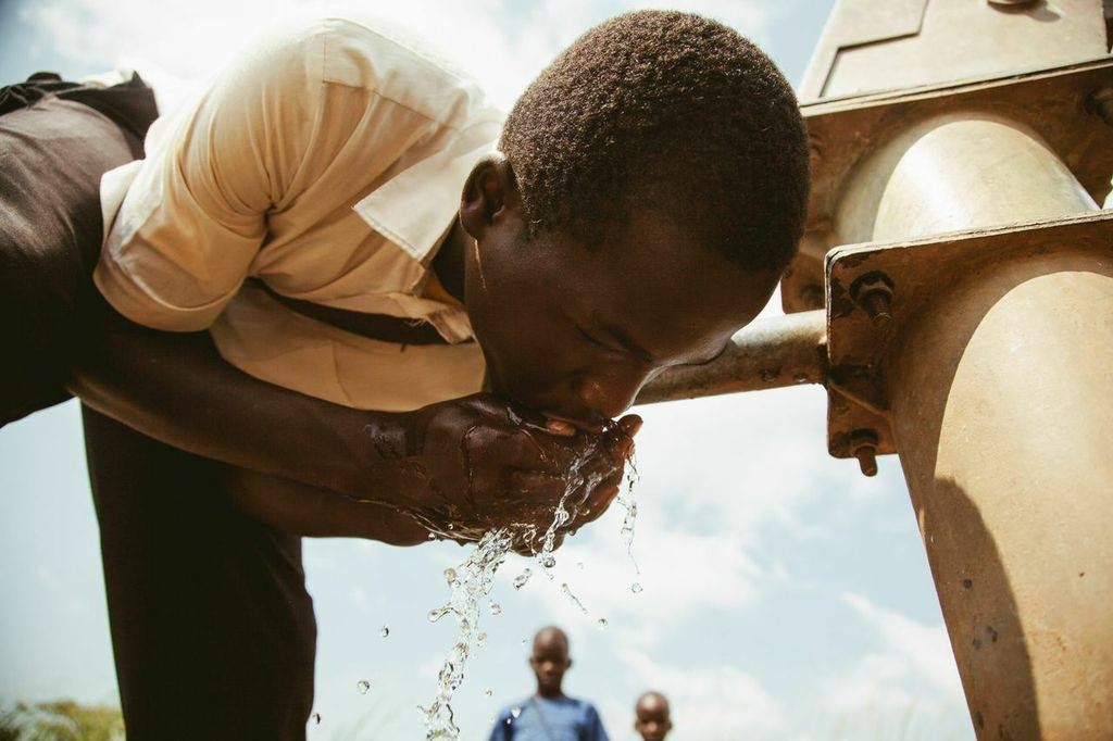 Boy drinking water from a tap in Uganda
