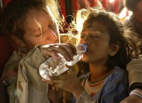 Woman giving daughter drink of water