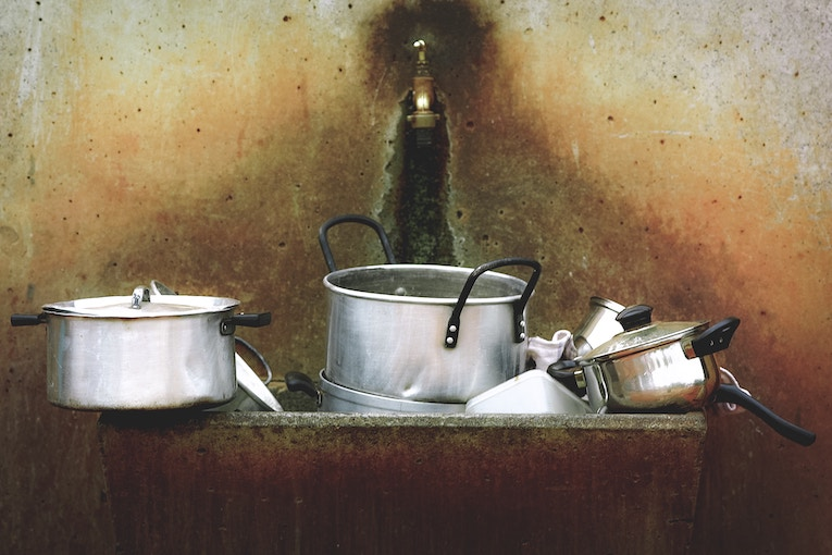 Pots and pans piled up in a sink in Africa